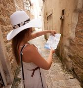 portrait of young woman looking at map on old narrow street - stock photo