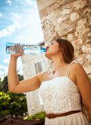 young brunette woman drinking water out of bottle at sunny day - stock photo