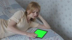 Beautiful girl using tablet pc with pre-keyed green screen lying on bed - stock footage