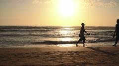 Bali, people walking and cycling on Kuta beach at sunset - stock footage