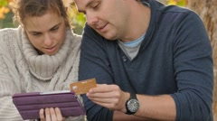 Couple using a tablet PC to purchase item via online shopping website app Stock Footage