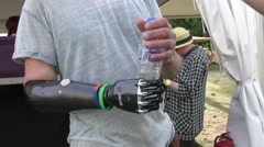 An amputee man demonstrates his  bionic BeBionic hand Stock Footage
