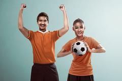 Happy couple football fan holding ball Kuvituskuvat