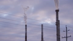 Chimney at industrial plant - smoke stacks on purple sky Stock Footage