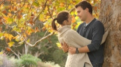 Autumn fall season romance young couple in love hug and cuddle under tree - stock footage