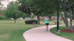 Woman Runner in City Park Stopping to Stretch Stock Footage