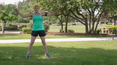 Woman Exercise Jumping Jacks in City Park Stock Footage
