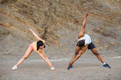Young mixed race couple doing exercise outdoor on the stoned beach. Sexy Stock Photos