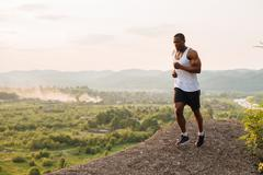 Sexy black muscular male model bodybuilder jogging outdoor. Green forest Stock Photos