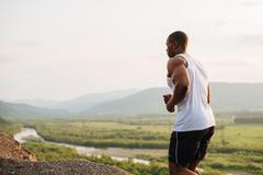 Black african american muscular male model bodybuilder jogging outdoor. Green Stock Photos