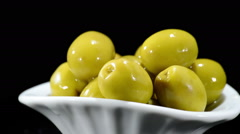 Green olives fruit gyrating on black background - stock footage