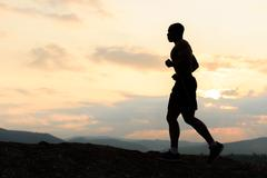 Silhouette of african american athlete jogging on sunset in mountains. Traini Kuvituskuvat