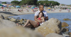 4K Attractive mixed ethnicity couple relaxing together at the beach Stock Footage