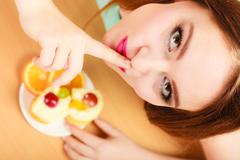 Woman eating cake showing quiet sign. Gluttony. Stock Photos