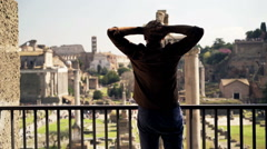Man stretching arms and admire view of the Roman Forum from balcony in Rome Stock Footage