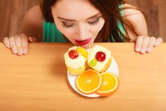 Woman looking at delicious sweet cake. Gluttony. - stock photo