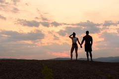 Silhouettes of athletic gymnastic couple watching the sunrise together. Beaut Stock Photos
