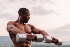 Handsome african american muscular man lifting dumbbells against the sunset s Kuvituskuvat