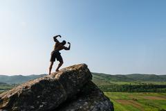 Portrait of african american bodybuilder with naked torso posing on the rock. Stock Photos