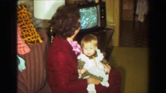 1969: Grandma baby watching American football on color tv on couch in living Stock Footage