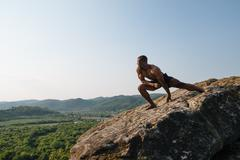 Strong african american bodybuilder is training on the rock in mountains. Gre Stock Photos