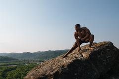 Strong handsome african american bodybuilder is training on the rock in mount Stock Photos
