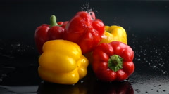 Water pouring on yellow and red peppers in slow motion Stock Footage