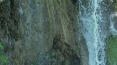 Waterfall falls from a cliff and splashing in a lake in slow motion Stock Footage