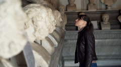 Young woman watching marble sculptures in Italian museum in Rome Stock Footage