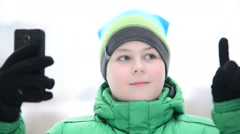 Boy uses cell phone with touchscreen gloves outside in winter Stock Footage