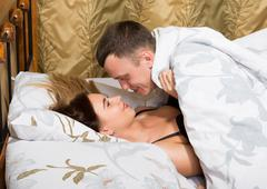 young couple lying on the bed in the hotel. the man leaned over young woman, his - stock photo