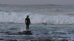 WOLLONGONG, AUSTRALIA  Young surfer with surfboard looking at waves Stock Footage