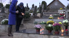 Man and woman light candle with matches on family member grave in cemetery. 4K - stock footage