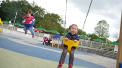 Happy little child girl have fun swaying on swing on children playgroung park Stock Footage