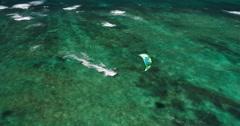 Aerial view of kitesurfer gliding across blue ocean Stock Footage