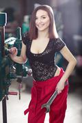 Nice sexy woman mechanic-engineer holding wrench. Girl weared in red work Kuvituskuvat