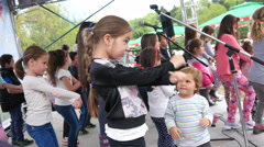Children kids dancing on a park stage entertain parents during family festival Stock Footage