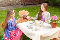 girls having tea party with teddy bear at yard - stock photo
