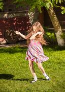Young girl dancing on grass at sunny day Stock Photos