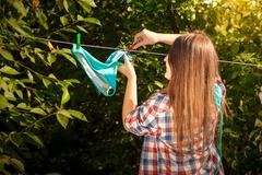 woman in shirt drying bikini on clothesline - stock photo