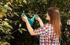 woman hanging blue bikini on clothesline at garden - stock photo