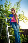 young girl standing on ladder at apple garden - stock photo