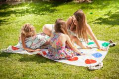 family with children playing twister at sunny day - stock photo
