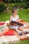 Small girl sitting on plaid and holding family photo album Stock Photos