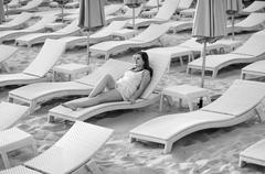Monochrome photo of sexy woman in dress lying on sunbed Stock Photos