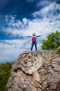 Beautiful woman standing on top of high cliff with stretched out hands Stock Photos