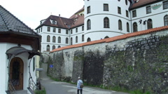 Tourist walks under the walls of a castle in Germany Stock Footage
