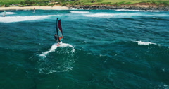 Aerial view of windsurfer gliding across blue ocean Stock Footage