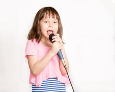 Asian girl singing with microphone - stock photo