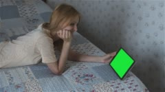 Beautiful girl watching movie on tablet with pre-keyed green screen lying on bed - stock footage